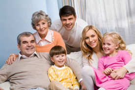 stock photo of father child  - Portrait of senior and young couples with their children looking at camera at home - JPG