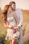 foto of lavender field  - Young beautiful sensual couple kissing outdoors in windy weather in the summer on a lavender field - JPG
