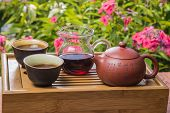 stock photo of poetry  - Chinese tea in the garden with beautiful flowers. Aromatic tea from a clay pot on the side with carved hieroglyphs of ancient poetry 
