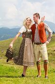 image of lederhosen  - Bavarian couple in fashionable lederhosen and dirndl having fun in a meadow in the mountains - JPG
