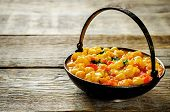 picture of chickpea  - curry chickpea with cauliflower and vegetables on a dark wood background. tinting. selective focus on the middle of curry