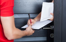 stock photo of fragile sign  - Woman signing parcel shipment documents on clipboard - JPG