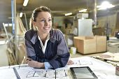 foto of carpenter  - Young woman carpenter designing plans in workshop - JPG