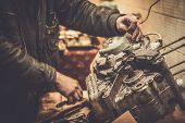 picture of motorcycle  - Mechanic working with with motorcycle engine in a workshop - JPG