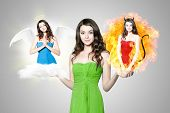 stock photo of hells angels  - Beautiful young brunette woman choosing between angel and devil - JPG