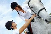 stock photo of horse riding  - Image of handsome man helping woman to sit on purebred horse - JPG