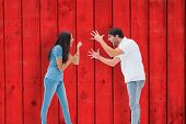 stock photo of shout  - Angry couple shouting at each other against red wooden planks - JPG