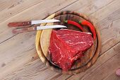 foto of red meat  - fresh raw beef meat steak chunk with red hot pepper on wood with stainless steel knife - JPG