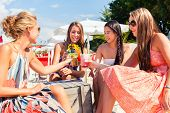 stock photo of sun-tanned  - Four woman sitting in beach bar - JPG