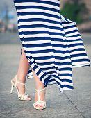foto of flutter  - Legs of woman dressed long fluttering striped dress outdoor in the city - JPG