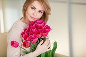 Постер, плакат: Happy woman with a bouquet of pink tulips