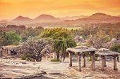 picture of karnataka  - Ancient ruins on Hemakuta hill at orange sunset sky in Hampi Karnataka India  - JPG