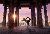 foto of karnataka  - Woman doing yoga in ruined ancient temple with columns Hampi Karnataka India  - JPG