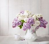 picture of jug  - Lilac Bouquet  in old ceramic jug  and cup of coffee   against a white wooden table - JPG