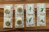 foto of brie cheese  - close up of slices of brie cheese on everything crackers with sliced of olives and fresh dill - JPG
