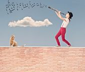 foto of clarinet  - little girl playing clarinet on the top of a bricks wall - JPG