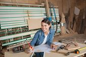 pic of carpenter  - Happy female carpenter working on blueprint while looking away in workshop - JPG