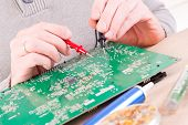 pic of multimeter  - Serviceman checks PCB with a digital multimeter in the service workshop - JPG