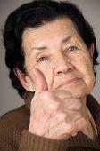 stock photo of grandma  - closeup portrait of grandma old woman holding thumb up over gray background selective focus  - JPG