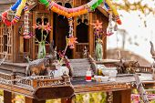 foto of religious  - a small thai buddhist temple or shrine with some religious offerings - JPG