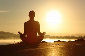 foto of yoga  - Silhouette of a fitness woman exercising yoga meditation exercises with the sun in the background - JPG