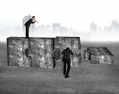 image of yell  - Boss using speaker yelling at employee pushing big jigsaw puzzle concrete blocks on concrete floor with cityscape skyline background - JPG