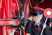 foto of train-wheel  - Little child boy as nostalgic railroad conductor with cap and signaling disk beside large wheels of a steam locomotive - JPG
