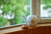 picture of bagel  - Old teapot and bagel are on a wooden windowsill - JPG