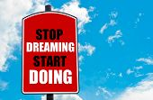 image of start over  - Stop Dreaming Start Doing motivational quote written on red road sign isolated over clear blue sky background - JPG