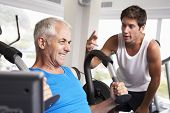 foto of encouraging  - Middle Aged Man Being Encouraged By Personal Trainer In Gym - JPG