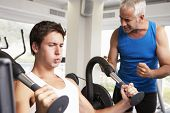 stock photo of encouraging  - Middle Aged Man Being Encouraged By Personal Trainer In Gym - JPG
