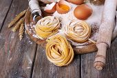stock photo of pasta  - Raw homemade pasta and ingredients for pasta on wooden background - JPG