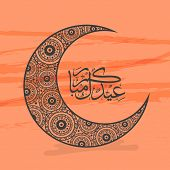 foto of arabic calligraphy  - Beautiful floral design decorated crescent moon with Arabic Islamic calligraphy of text Eid Mubarak on orange background - JPG
