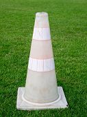 stock photo of pale  - Pale traffic cone on the lawn background - JPG