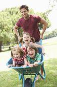 picture of wheelbarrow  - Father Giving Children Ride In Wheelbarrow - JPG