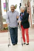 stock photo of wifes  - Wife Helping Senior Husband To Use Walking Frame - JPG