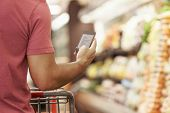 foto of supermarket  - Close Up Of Man Reading Shopping List From Mobile Phone In Supermarket - JPG