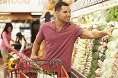 pic of supermarket  - Man Pushing Trolley By Produce Counter In Supermarket - JPG