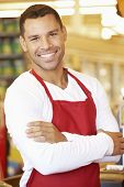 image of cashiers  - Male Cashier At Supermarket Checkout - JPG