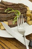 image of flank steak  - Sliced juicy skirt steak with potatoes and arugula garnish - JPG