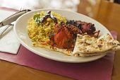stock photo of tamarind  - Indian tandoori chicken with fresh naan and tamarind rice - JPG