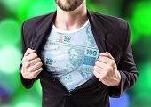 image of brazilian money  - Businessman stretching suit with Brazilian money on bokeh background - JPG
