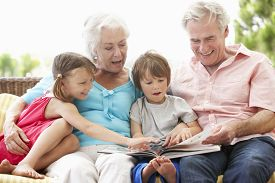 picture of grandparent child  - Grandparents And Grandchildren Reading Book On Garden Seat - JPG