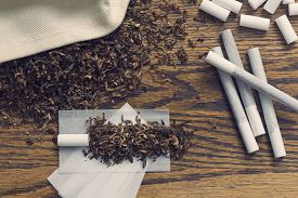 image of tobacco smoke  - Rolling cigarettes with filters papers and plenty finely cut tobacco - JPG