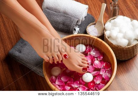 poster of Closeup photo of a female feet at spa salon on pedicure procedure. Female legs in water decoration the flowers.
