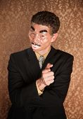 stock photo of hustler  - Masked businessman on damask background pointing straight ahead - JPG