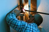 stock photo of sphincter  - sphincter working on metal pipe with welding machine - JPG