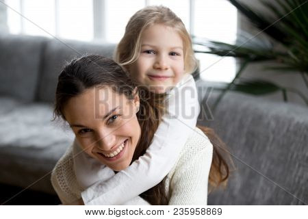 poster of Happy Single Mother Laughing Piggybacking Little Girl At Home, Smiling Mom And Daughter Having Fun P