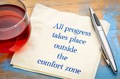 All progress takes place outside the comfort zone - inspiraitonal handwriting on a napkin with a cup poster