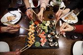 A Set Of Sushi Rolls On A Table In A Restaurant. A Party Of Friends Eating Sushi Rolls Using Bamboo  poster